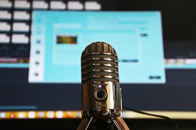 Professional microphone in front of a computer monitor.