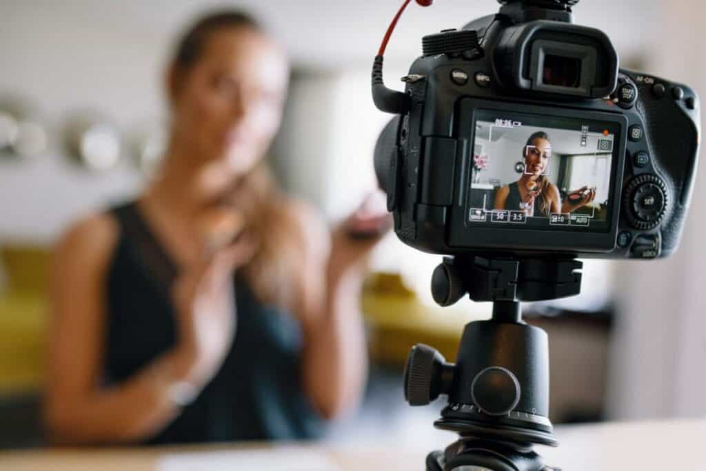 Woman recording herself on a camera showcasing her product for her business.